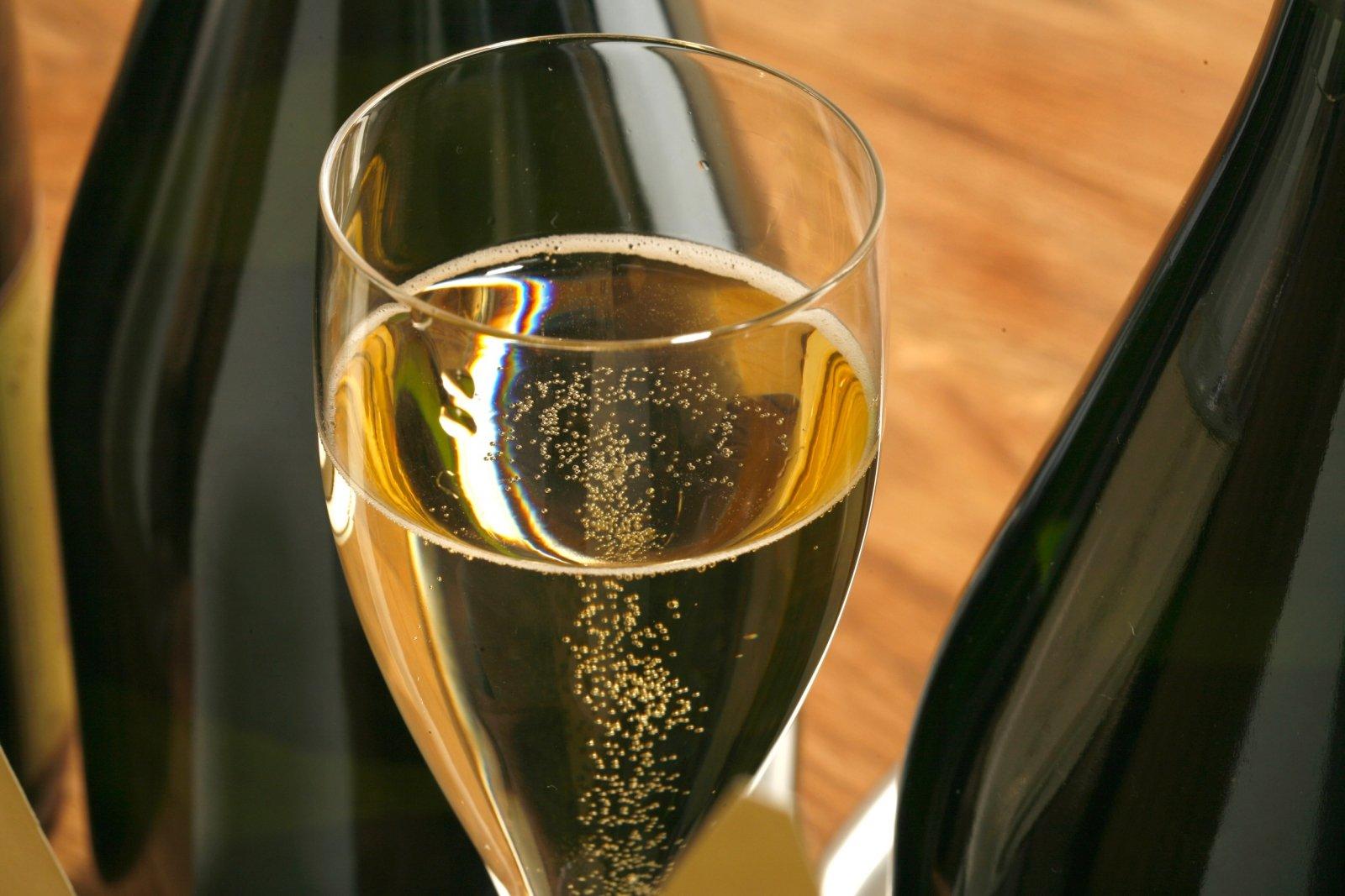 Plan rapproché sur une coupe de Champagne entre 2 bouteilles